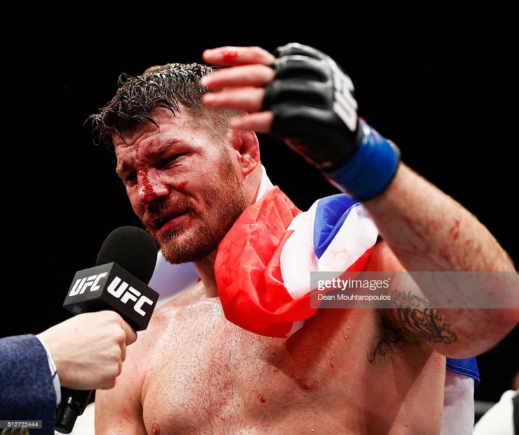 A bloody and battered Michael 'The Count' Bisping of England celebrates victory over Anderson 'The Spider' Silva of Brazil in their Middleweight bout...
