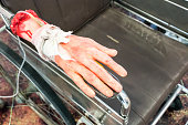 Bloody and creepy halloween toy, fake human hand tied with saline drip on wheel chair for halloween hospital theme.