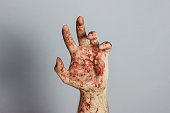 bloody hand in front of grey background