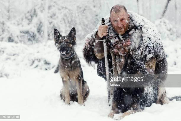 Blutige Wikinger-Krieger im Winter Schneesturm mit Jagdhunden