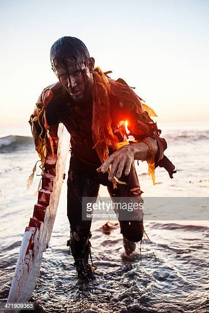 Bloody zombie with one crab hand emerging from the ocean