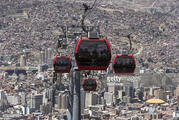 Travelers ride on red line Mi Teleferico cable cars above the city in La Paz Bolivia on Thursday Sept 8 2016 Boliva's Mi Teleferico cable cars are...