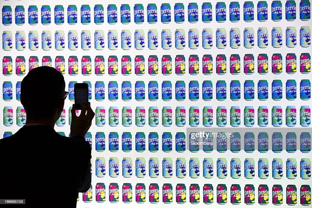 Bloomberg Photo Service 'Best of the Week': An attendee uses a smartphone to photograph an illuminated advert for Nestle SA's Perrier water ahead of the company's annual general meeting (AGM) in Lausanne, Switzerland, on Thursday, April 11, 2012. Nestle SA's chairman said Switzerland is becoming more difficult as a business location after voters last month approved some of the world's toughest limits on executives' pay. Photographer: Valentin Flauraud/Bloomberg via Getty Images