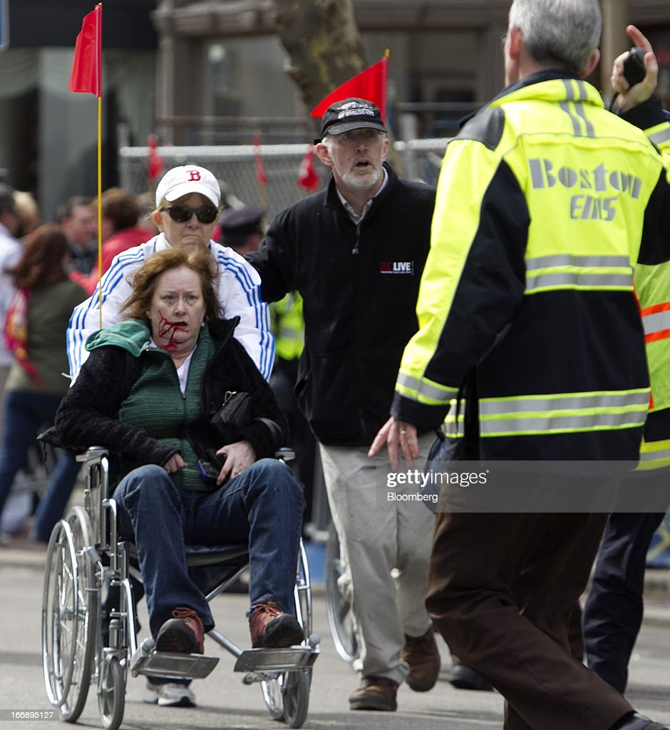 Bloomberg Photo Service 'Best of the Week': First responders transport an injured woman in a wheelchair where two explosions occurred along the final stretch of the Boston Marathon on Boylston Street in Boston, Massachusetts, U.S., on Monday, April 15, 2013. Two powerful explosions rocked the finish line area of the Boston Marathon near Copley Square and police said many people were injured. Photographer: Kelvin Ma/Bloomberg via Getty Images