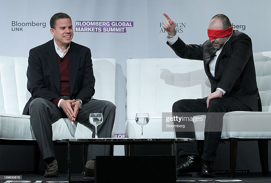 Bloomberg Television & Radio anchor Pimm fox, right, tries to guess his mystery guest, Andrew Young III, chief executive officer of GiveLocally, while blindfolded at the Bloomberg Global Markets Summit in New York, U.S., on Thursday, Jan. 17, 2013. The Bloomberg Global Markets Summit, co-hosted by Foreign Affairs Magazine and Bloomberg LINK, convenes market makers and market movers as investors map their strategy for the year ahead. Photographer: Jin Lee/Bloomberg via Getty Images