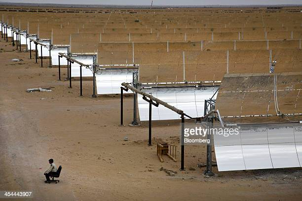 Bloomberg's Best Photos 2013 A security guard sits beside an array of parabolic troughs at the Godawari solarthermal power plant operated by Godawari...