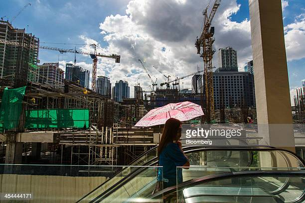 Bloomberg's Best Photos 2013 A woman carrying an umbrella rides an escalator past a construction site in the Fort Bonifacio district of Manila the...
