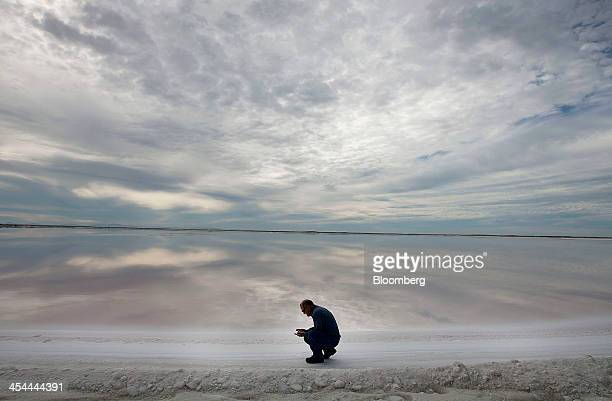 Bloomberg's Best Photos 2013 Biologist Fernando Heredia inspects the quality of a crystallization pond at the Exportadora de Sal harvest fields in...