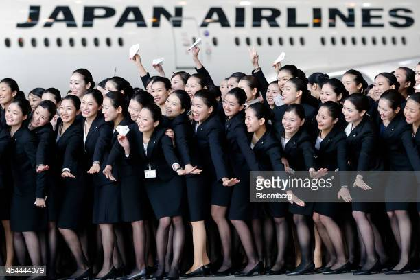 Bloomberg's Best Photos 2013 Japan Airlines Co group companies' new employees pose for photographs in front of a JAL aircraft during a welcoming...