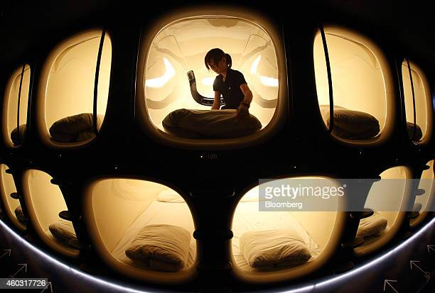 Bloomberg's Best Photos 2014 An employee makes a bed inside a capsule unit in the Nine Hours Narita Airport capsule hotel operated by nine hours Inc...