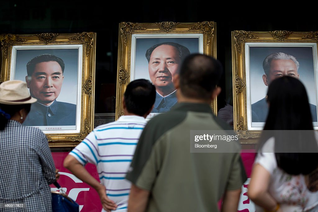 Bloomberg's Best Photos 2014 People look at portraits of former Chinese leaders Zhou Enlai left Mao Zedong center and Liu Shaoqi displayed in a shop...