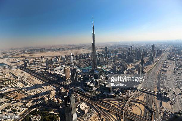 Bloomberg's Best Photos 2014 The Burj Khalifa tower center is surrounded by other skyscrapers in this aerial view of the city skyline and the desert...