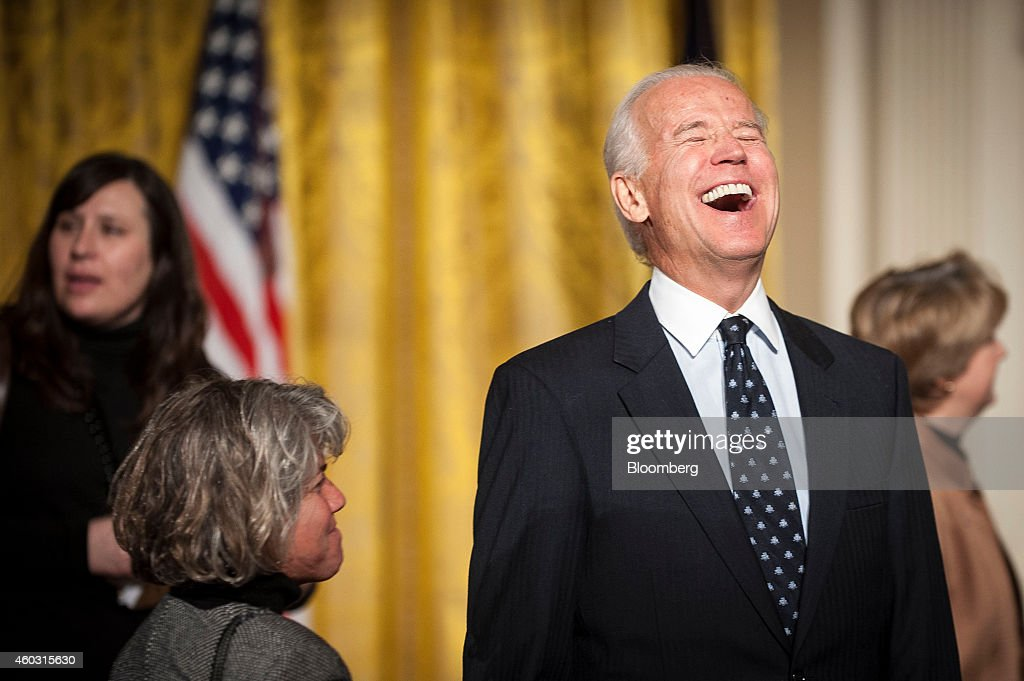 Bloomberg's Best Photos 2014: U.S. Vice President Joe Biden, right, laughs during an event for the Council on Women and Girls in the East Room of the White House in Washington, D.C., U.S., on Wednesday, Jan 22, 2014. U.S. President Barack Obama signed a presidential memorandum establishing a White House task force to protect students from sexual assault. Photographer: Pete Marovich/Bloomberg via Getty Images