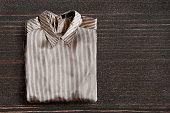 Folded striped satin blouse on dark wooden background