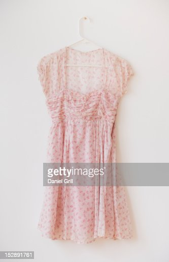 Blouse with floral pattern on hanger against white wall