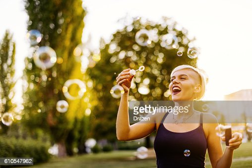 Blowing bubbles in the park in summer