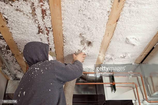 Blown Insulation being Installed between Floor Joists