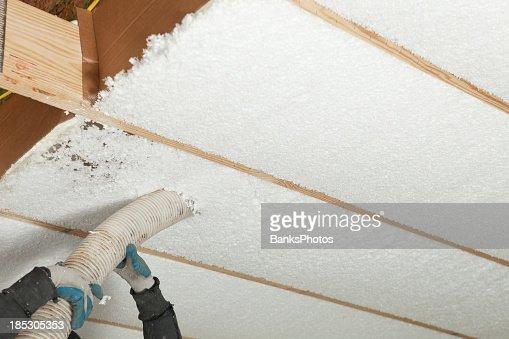 Blown insulation being installed between floor joists for Floor joist insulation