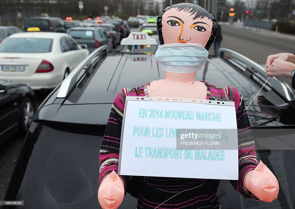 A blow-up doll is set up on a taxi driver's car on January 10, 2013 in Strasbourg, eastern France during a nationwide demonstration to protest against legislative changes concerning the transport of sick and incapacitated passengers. Cardboard reads 'in 2014 a new market for delivery companies, transporting sick people'. AFP PHOTO/FREDERICK FLORIN