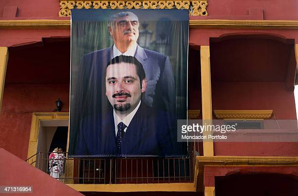 A blowup of Rafik alHariri with his son with Saad Hariri standing on a building in the city The former premier was killed by a car bomb the 14th...