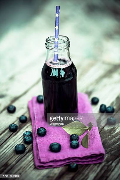 Bluberry juice in glass bottle, drinking straw