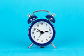 single alarm clock on blue background