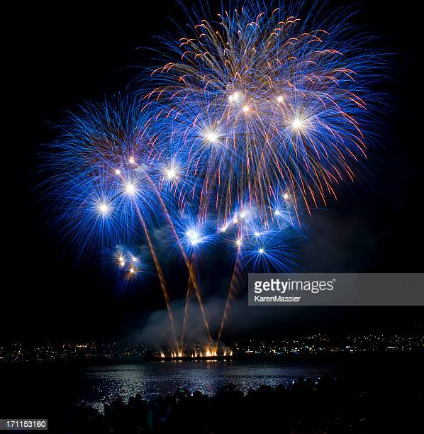 Blue and orange fireworks at night over a lake