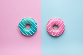 Colorful sweet background. Blue and pink donuts on pink and blue background.