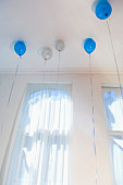 Blue and white balloons on ceiling of room