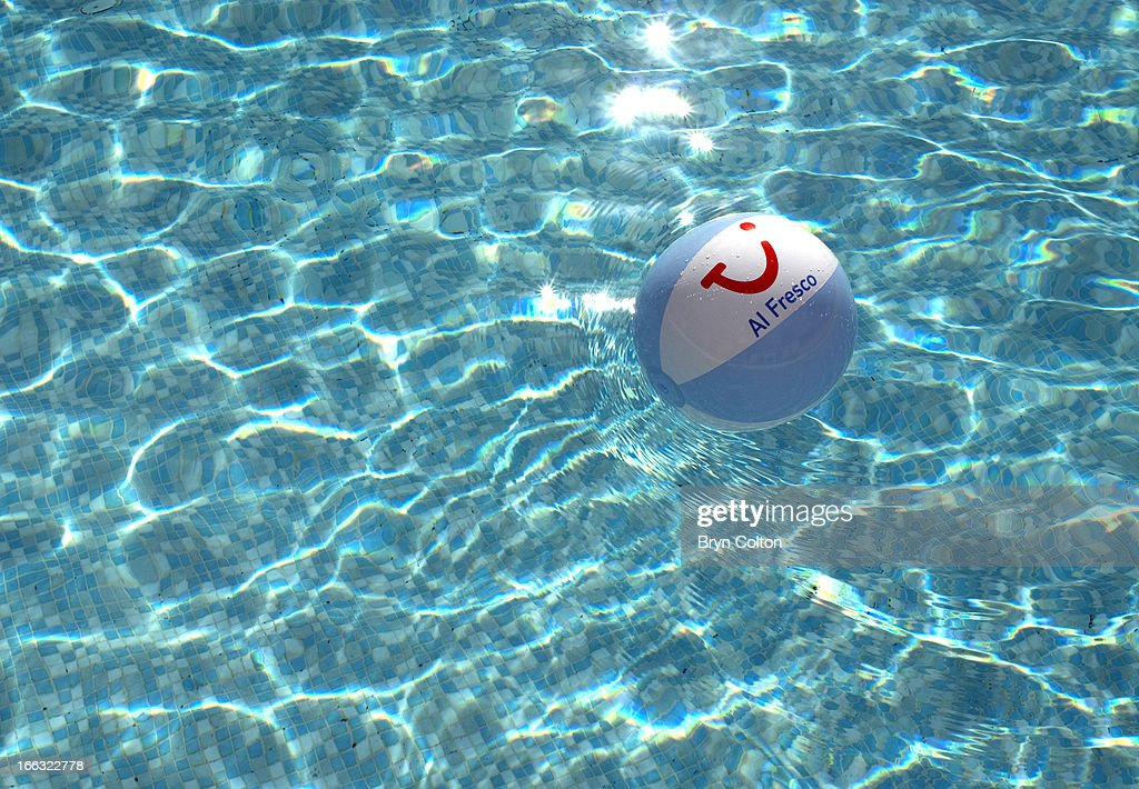 A blue and white beach ball, bearing the corporate branding for Tui Travel Plc, the leisure group, is seen floating in a swimming pool at a French campsite near Saint-Jean-de-Monts, Vendee, France, on Friday, August 18, 2006. Tui Travel Plc operates as an international leisure travel group in the European and North American market.