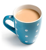 English breakfast tea with a splash of milk in a blue mug with spots isolated on a white background. English breakfast tea is a black tea used to make aromatic beverage. The drink is prepared by pouri