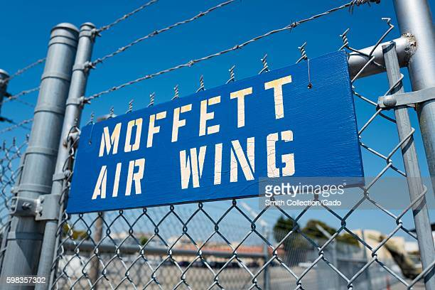 Blue and white stenciled sign for the Moffett Air Wing hanging on a barbed wire fence at Moffett Field within the secure area of the NASA Ames...