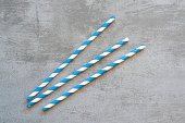 Blue and white striped drinking straws on concrete background