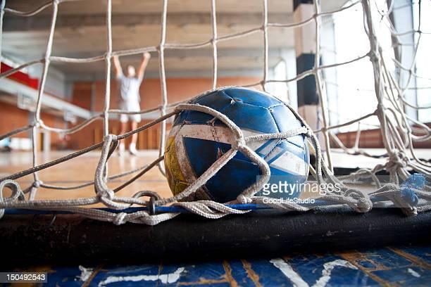 Blue and yellow handball inside of goal net