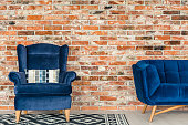 Industrial style brick wall, blue armchair, sofa and pattern rug