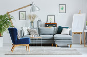 Blue armchair on grey carpet in designer's living room with lamp, easel and grey sofa