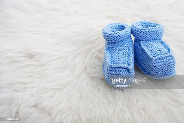 Blue baby shoes on sheepskin
