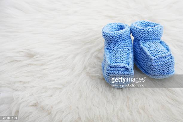 Blue baby shoes on sheepskin