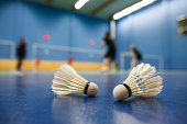 badminton courts with players competing; shuttlecocks in the foreground (shallow DOF; color toned image)