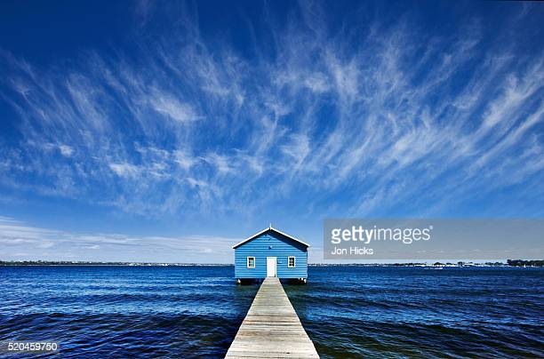 Blue boathouse on the end of a jetty