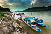 Blue boats on the Mekong river at sunset