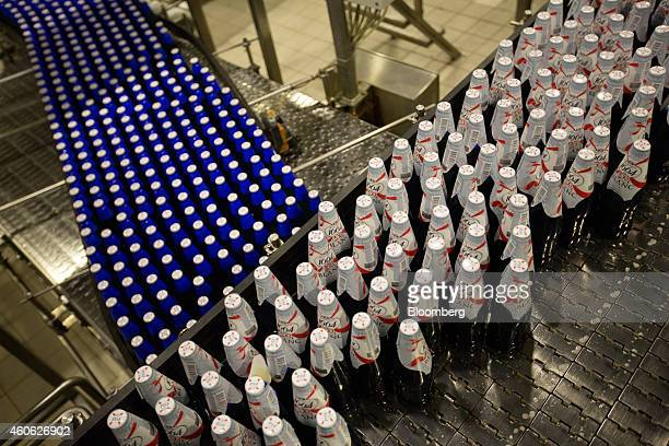 Blue bottles of Kronenbourg 1664 Blanc beer move along the production line during the labelling process at the OAO Baltika brewery operated by...