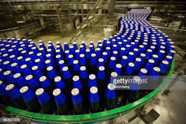 Blue bottles of Kronenbourg 1664 Blanc beer move along the production line ahead of labelling at the OAO Baltika brewery operated by Carlsberg A/S in...
