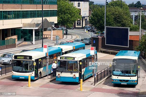 Blue buses waiting at a station in a small city