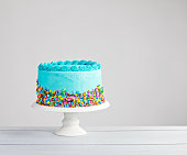 Blue buttercream cake with colorful sprinkles over a light grey background.
