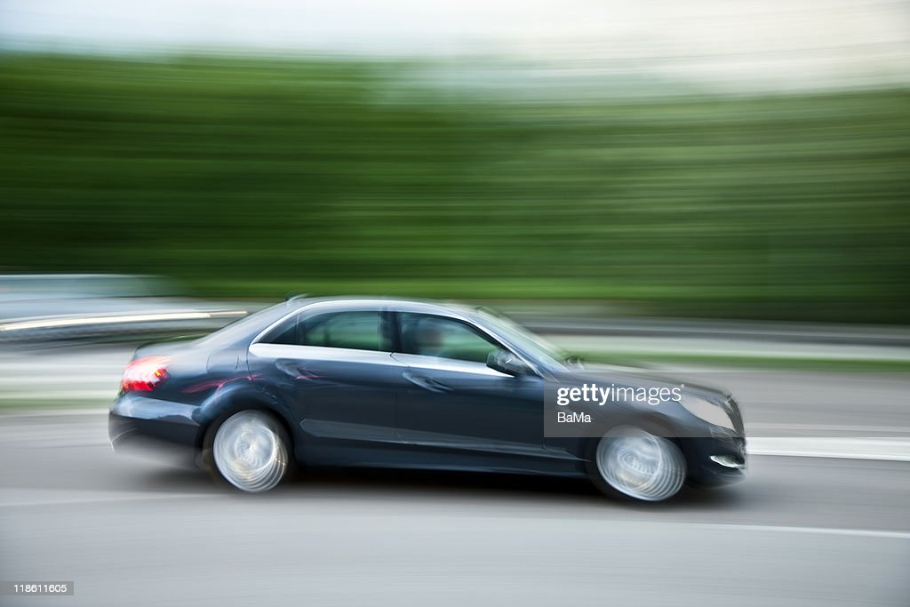 Blue Car Speeding on Highway at Dusk : Stock Photo