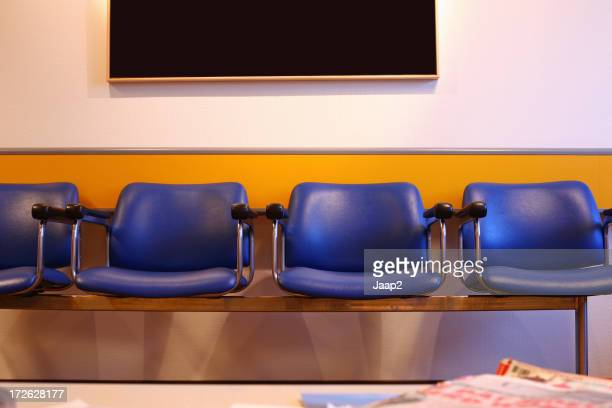 Blue chairs in waiting room with blank painting on wall