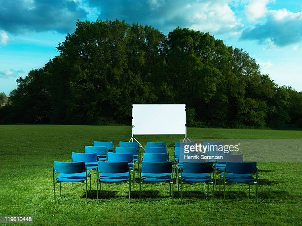 blue chairs on field in front of white screen