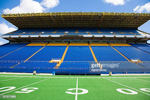 Blue chairs with no audience at a football stadium