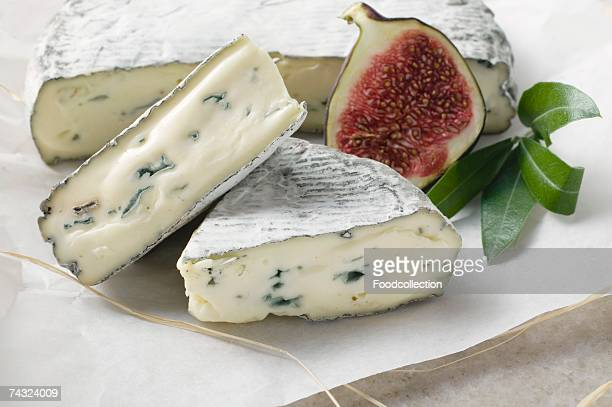 Blue cheese with pieces cut and half a fig on paper